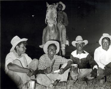 Group of five Aboriginal stockmen on horseback at night camp.