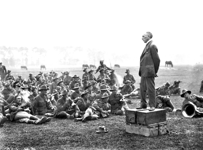 The Australian Prime Minister, Right Honourable William Morris (Billy) Hughes (standing on four ammunition boxes), addressing Australians, about one and a half miles from Amiens.
